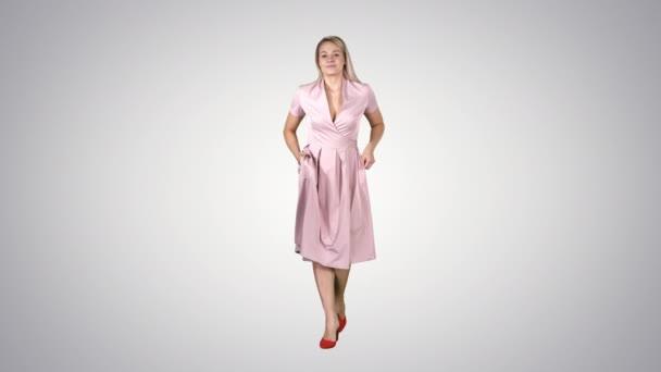 Frau in rosa Kleid mit Händen in Taschen geht auf Steigungsuntergrund auf die Kamera zu.