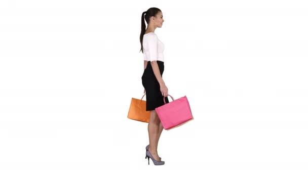 Young woman with shopping bags walking out from shop on white background.