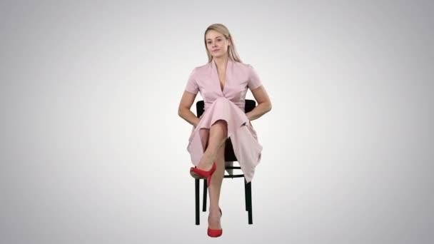 Krásná mladá žena, dívka, model Blondýna s dlouhými vlasy, sedí na židli a při pohledu do kamery na pozadí s přechodem.
