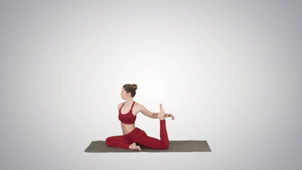 Beautiful young woman wearing red sportswear doing yoga or pilates exercise One Legged King Pigeon pose, Eka Pada Rajakapotasana on gradient background.