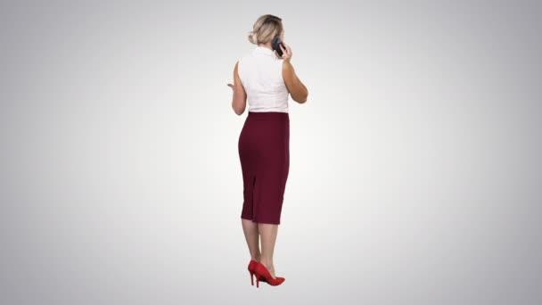 stehende junge schöne Frau mit einem Mobiltelefon, das einen Anruf auf dem Gefällehintergrund macht.