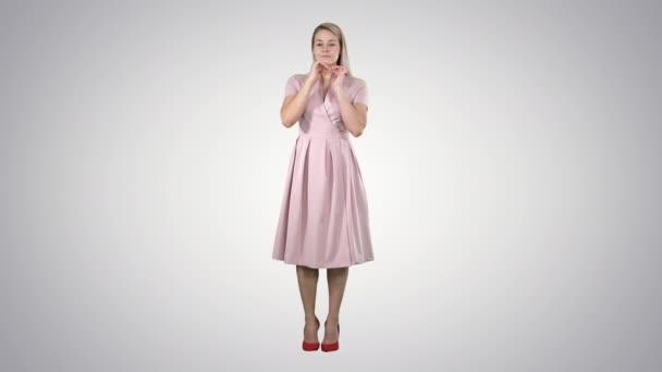 Krásná nabídka dívka v růžových šatech pohledu do zrcadla na pozadí s přechodem.