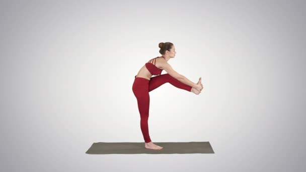 Beautiful young fit woman in sportswear doing sport exercise, bending in variation of Utthita Hasta Padangusthasana, Dandayamana-Janushirasana on gradient background.