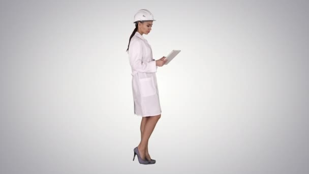 Young woman engineer walking with tablet looking at objects around on gradient background.