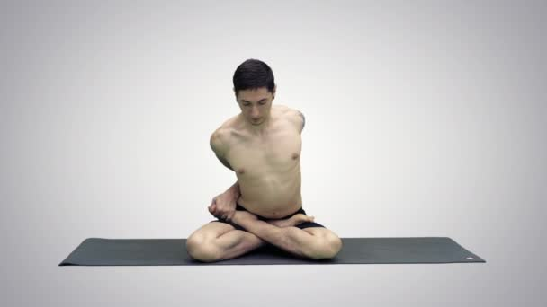 sportliche schöne junge Mann praktiziert Yoga, sitzt im Schneidersitz in adho mukha padmasana, beugt sich nach vorne in Variation der Lotus-Pose auf Steigungsuntergrund.