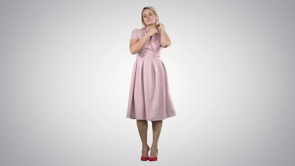Schöne Dame in rosa Kleid preen auf Gradienten Hintergrund.