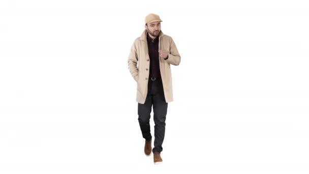 sprechender junger Mann im Trenchcoat spricht selbstbewusst in die Kamera und bewegt sich einfach vorwärts auf weißem Hintergrund.