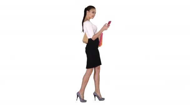 Mladá žena s nákupní tašky mluvit na mobilním telefonu na bílém pozadí