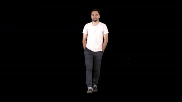 Magabiztos, fiatal felnőtt férfi, aki előre sétál és fehér inges kamerába néz, Alpha Channel