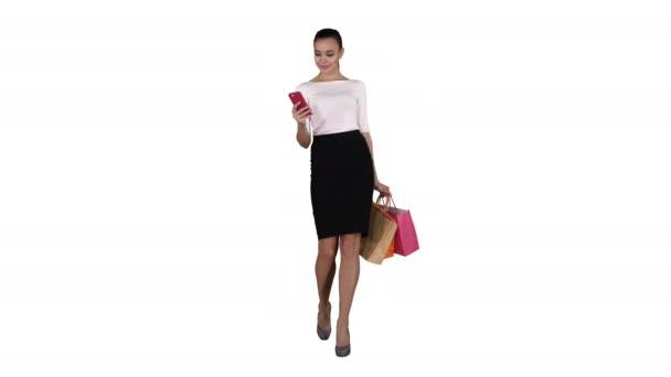 Krásná mladá žena pomocí mobilního telefonu textování na bílém pozadí.