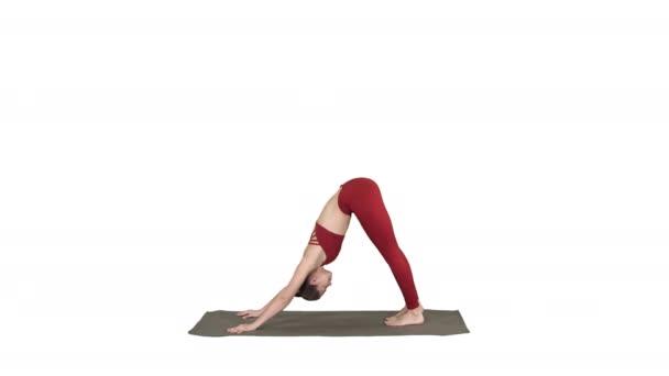 Krásná mladá žena nosí červené sportovní dělá jógu nebo pilates cvičení, stojící v variace Natarajasana na bílém pozadí.