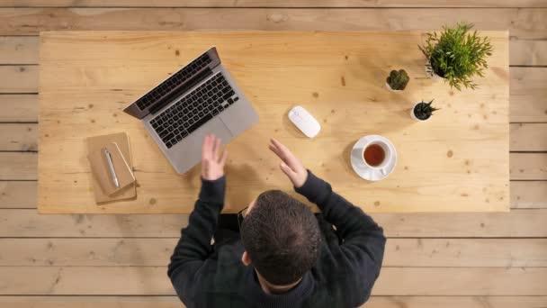 Šťastné vousatý bederní chlápek mává rukou a mluví na video chat pomocí vysoké vysokorychlostní internet pro dobré připojení na notebook.