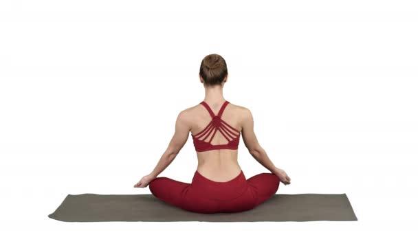 Gesunde junge Frau sitzt in Lotus-Pose auf weißem Hintergrund.