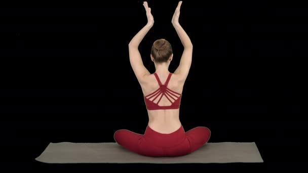 Mladá sportovní žena sedící v lotosové póze, spojte ruce nad hlavou, alfa kanál