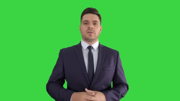 Handsome businessman presenting to camera giving three points on a Green Screen, Chroma Key.