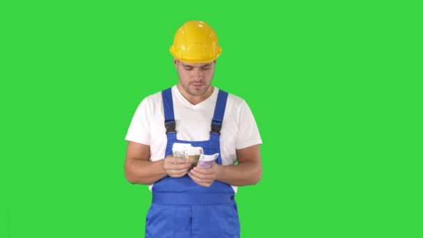 Builder counting money standing on a Green Screen, Chroma Key.