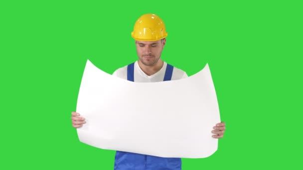 Építőipari munkás ellenőrző tervezeteket a helyszínen egy zöld képernyő, chroma key.