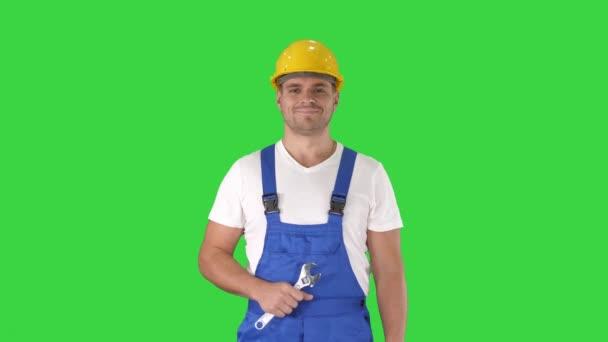 Pracovník s klíčem ukazujícím palec nahoru a s úsměvem na kameru na zelené obrazovce, Chroma Key.