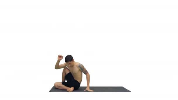 Muž cvičí jógu, protahuje trup na bílém pozadí.