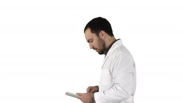 Portrait of male doctor walking and using digital tablet on white background.