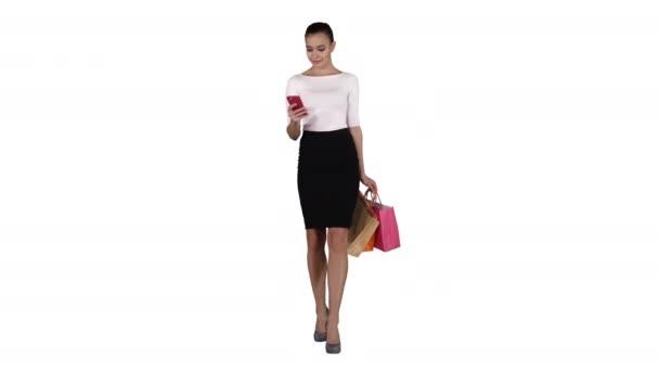 glückliche junge Frau mit Smartphone macht Bild ihrer Einkaufstüten auf weißem Hintergrund.