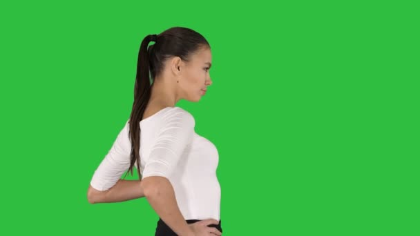 Beautiful brunette girl walking with hands on hips on a Green Screen, Chroma Key.