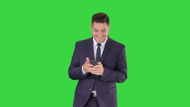 Businessman on the phone typing text message walking on a Green Screen, Chroma Key.