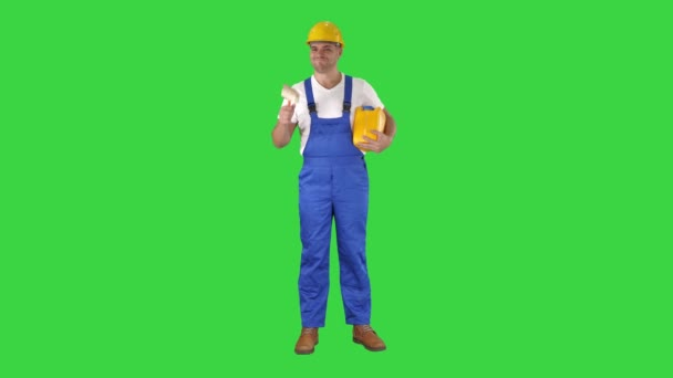 Worker holding paint brush smiling to camera on a Green Screen, Chroma Key.