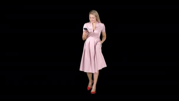 Young woman in pink looking at mobile smartphone and texting something while walking, Alpha Channel