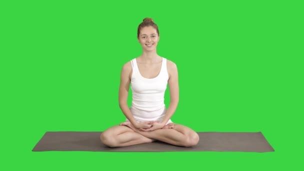 Krásná žena v bílých plápajících, sedící na rohoži a mluvení s kamerou na zelenou obrazovku, klíč Chroma.