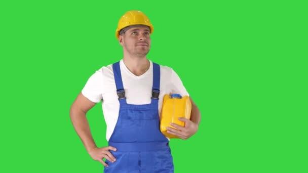Šťastný pracovník v tvrdé čepici drží palce nahoru renovace na zelené obrazovce, chroma klíč.