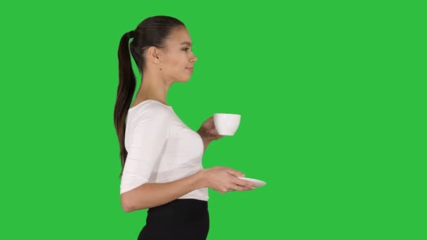 Beautiful brunette woman with white mug with tea or coffee walking on a Green Screen, Chroma Key.
