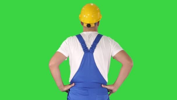 Inženýr ve stavební přilbě, stojící v bocích a rozhlížel se po zelené obrazovce, klíč Chroma.