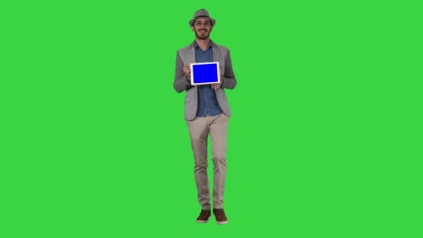 Casual man in a hat walking and showing digital tablet to camera on a Green Screen, Chroma Key.