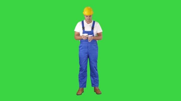 ein Arbeiter zählt aufgeregt sein Gehalt auf einem grünen Bildschirm, Chroma-Schlüssel.
