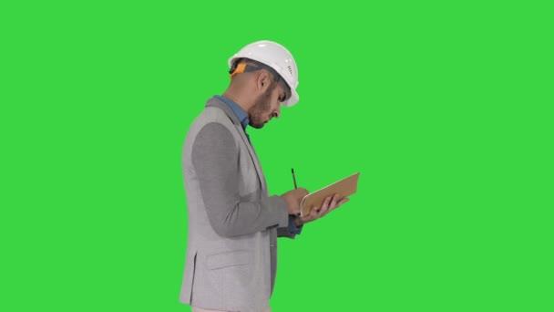 Arabský muž v příležitostných šatech a tvrdé čepici psaní seznam na zelené obrazovce, klíč Chroma.