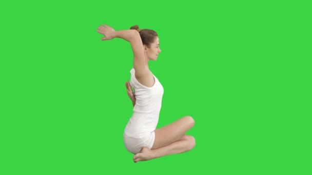 Yoga or pilates exercise without mat Gomukasana, Cow Face pose on a Green Screen, Chroma Key.