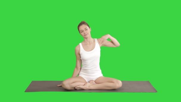 Krásná ženská cvič jómu v lotosové pozici, ruku nad hlavou, opřenou o jednu stranu a druhou na zelené obrazovce, chroma klíč.