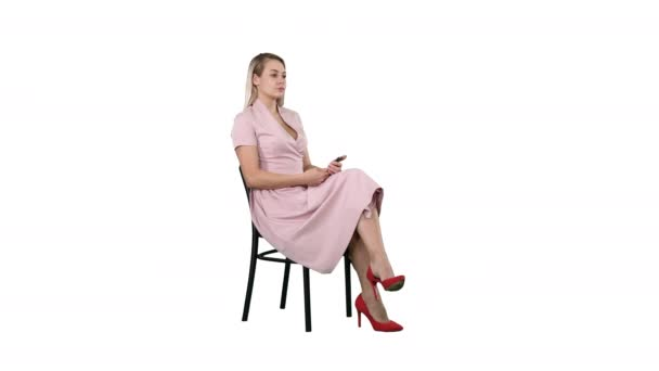 Woman in pink dress sitting on a chair waiting for someone on white background.