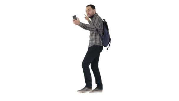 Young happy smiling man with backpack recording vlog blog with his phone on white background.