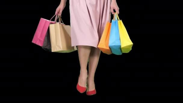 Fiatal nő lábak cipelő színes bevásárló táskák, Alpha Channel