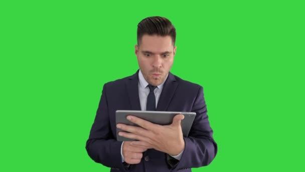 Schockierter Geschäftsmann beobachtet somethng auf digitalen Tablet auf einem grünen Bildschirm, Chroma Key.