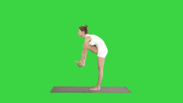 Beautiful young fit woman in sportswear doing sport exercise, bending in variation of Utthita Hasta Padangusthasana, Dandayamana-Janushirasana, Standing Head to Knee Bikram posture on a Green Screen