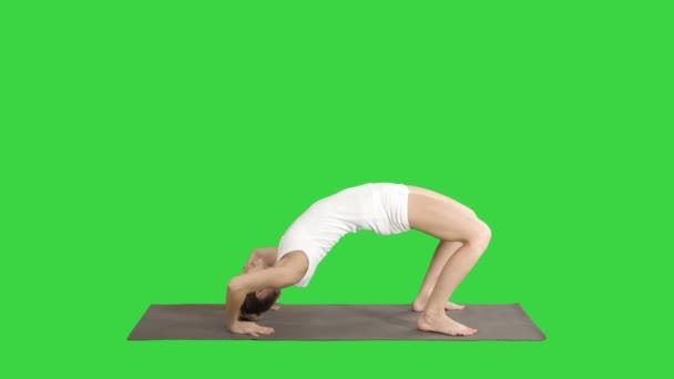 sportliche Yoga-Mädchen, die Chakrasana Urdva Dhanurasana Rad auf einem grünen Bildschirm posieren, Chroma-Taste.