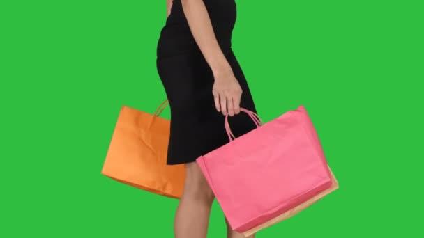 Mladá žena s nákupními taškami vycházející z obchodu na zelené obrazovce, Chroma Key.