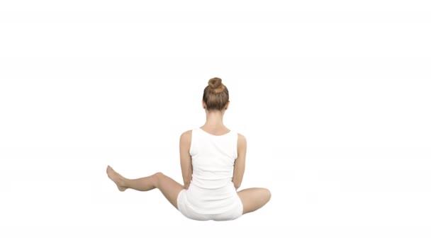Krásná mladá žena nosí sportovní oblečení a cvičila jóga, jak sedí v lotosové pozici na bílém pozadí.