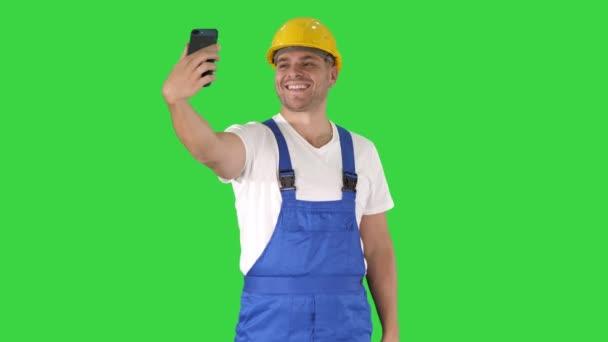 Usměvavý pohledný mladý stavitel s mobilním telefonem na zelené obrazovce, klíč Chroma.