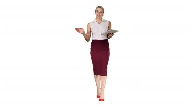 Üzleti nő táblagéppel séta és beszél a kamera fehér háttér.