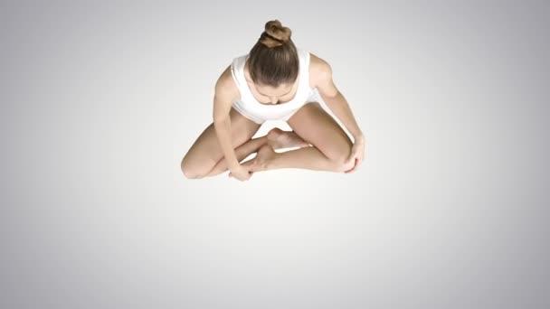 Fiatal nő meditál Lotus Pose gradiens háttér.