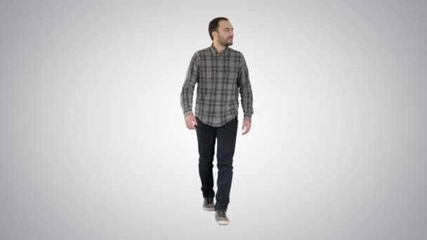 Relaxed casual man in jeans and shirt walking and looking to the sides on gradient background.